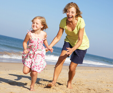 Woman playing with little girl on beach